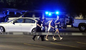An officer walks with people near the scene of a shooting at the Grand Theatre on Thursday, July 23, 2015, in Lafayette, La. (Leslie Westbrook/The Advocate via Associated Press)