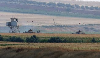 Turkish army tanks hold positions near the border with Syria, in the outskirts of the village of Elbeyi, east of the town of Kilis, in southeaster Turkey, Thursday, July 23, 2015. Suspected Islamic State militants fired at a Turkish military outpost from a region under IS control, inside Syrian territory Thursday, killing a Turkish soldier and wounding two others, an official said. Turkish troops retaliated to the attack and at least one IS militant was killed, amid a surge of violence in Turkey following a suicide bomb attack near Turkey's border with Syria which killed 32 people. (AP Photo/Emrah Gurel)