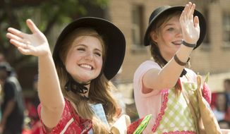 In this July 24, 2014, photo, Marin Allen and Ashlyn Bunker participate in the Days of 47 Pioneer Parade in Salt Lake City. Each year on July 24, Mormons take off work to gather at festive parades celebrating their heritage on Pioneer Day. Non-Mormons have invented their own counter-holiday around pies and beer. (AP Photo/The Salt Lake Tribune, Rick Egan)