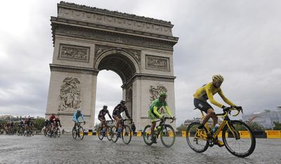 Britain's Chris Froome, right, wearing the overall leader's yellow jersey cycles past the Arc de Triomphe during the twenty-first and last stage of the Tour de France cycling race over 109.5 kilometers (68 miles) with start in Sevres and finish in Paris, France, Sunday, July 26, 2015. (AP Photo/Laurent Cipriani)
