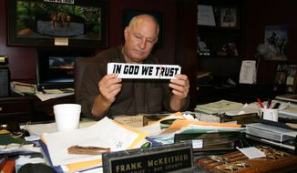 "Bay County Sheriff Frank McKeithen holds an ""In God We Trust"" bumper sticker. (Tom Quimby photo)"