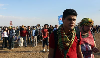 About 1,000 Kurdish activists from Istanbul who arrived in response to a call for mass mobilization by the imprisoned leader of the PKK rebel group, Abdullah Ocalan, gather at the border near Suruc, Turkey, on Sept. 25, 2014. (Associated Press)