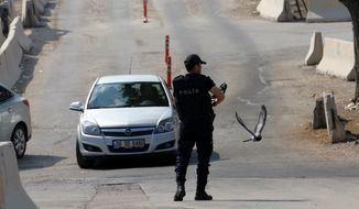 A police officer patrols as Turkish police raid homes in the Haci Bayram neighborhood of the capital Ankara, Turkey, Monday, July 27, 2015. (AP Photo/Burhan Ozbilici)