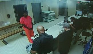 In this undated frame from video provided by the Waller County Sheriff's Department, Sandra Bland stands before a desk at Waller County Jail in Hempstead, Texas. Texas authorities on Tuesday, July 28, 2015, released several hours of footage showing Bland during her three days in jail, saying they wanted to dispel rumors that she was dead before arriving there. (Waller County Sheriff's Department via AP)