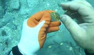 A diver finds rare coins from a 1715 shipwreck of the coast of Florida. (Image: Florida Today video screenshot) ** FILE **