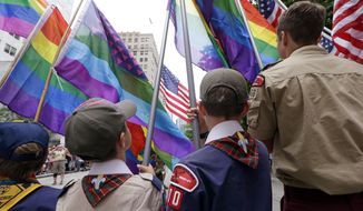 In this Sunday, June 28, 2015 photo, Cub Scouts and Boy Scouts prepare to lead marchers while waving rainbow-colored flags at the 41st annual Pride Parade in Seattle, two days after the U.S. Supreme Court legalized gay marriage nationwide. On Monday, July 27, 2015, the Texas-based Boy Scouts of America ended its blanket ban on gay adult leaders but will allow church-sponsored Scout units to maintain the exclusion for religious reasons. (AP Photo/Elaine Thompson/File)