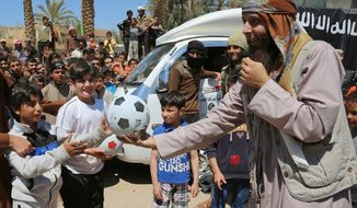 In this photo released on Jan. 14, 2015, by a militant website, which has been verified and is consistent with other AP reporting, an Islamic State militant, right, gives a ball to a boy, left, during a street preaching event in Tel Abyad in Raqqa province, northeast Syria. IS extremists have made it a priority to mold children under their rule into a new generation of militants, luring them into becoming fighters, suicide bombers and executioners. (Militant website via AP)