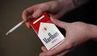 In this photo taken July 17, 2015, store manager Stephanie Hunt poses for photos with a pack of Marlboro cigarettes, an Altria brand, at a Smoker Friendly shop in Pittsburgh. (AP Photo/Gene J. Puskar) ** FILE **