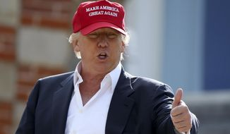 Presidential contender Donald Trump speaks to the media after arriving by helicopter during the first first day of the Women's British Open golf championship on the Turnberry golf course in Turnberry, Scotland, on July 30, 2015. (Associated Press)