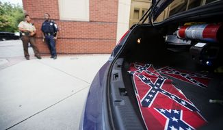 Confederate flags sit in the back of a police car as an Atlanta police officer and U.S. Park Ranger stand by outside Ebenezer Baptist Church in Atlanta on July 30, 2015. U.S. authorities are investigating after several Confederate battle flags were discovered near the church and a civil rights center named after Martin Luther King, an iconic leader in the African-American Civil Rights Movement. (Associated Press)