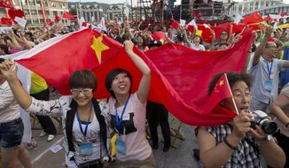 Residents celebrate after Beijing is announced as the host city for the 2022 Winter Olympics at the ski resort region of Chongli where the Nordic skiing, ski jumping, and other outdoor Olympic events will be held in northern China's Hebei province Friday, July 31, 2015. Beijing was selected Friday to host the 2022 Winter Olympics, becoming the first city awarded both the winter and summer games. (AP Photo/Ng Han Guan)