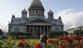 A couple share a tender moment in a park in front of the St. Isaac's Cathedral in St. Petersburg, Russia, Friday, July 31, 2015. (AP Photo/Dmitry Lovetsky) ** FILE **