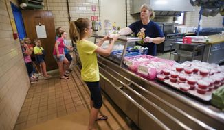 In this June 17, 2015 photo, Julie Finley, right, head cook for Windsor Schools, serves up meals at Windsor Elementary School in Windsor, Ill. The school participates is a summer lunch program after the district became eligible to participate when the percentage of low-income students it serves at the elementary school increased to more than 50 percent of the population. (Kevin Kilhoffer/Journal Gazette via AP)