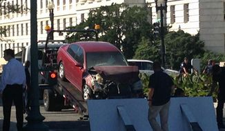 A car is is moved after crashing into a barrier on Capitol Hill in Washington, Friday, July 31, 2015.  Police say a person is in custody after a vehicle struck a barricade near the U.S. Capitol. Capitol Police say in a statement Friday morning that they're investigating after a vehicle hit the south barricade at the entrance to the Capitol grounds. Police say the driver, the only person in the vehicle, was taken into custody. (AP Photo/Alan Fram)