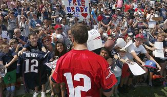 New England Patriots quarterback Tom Brady signs autographs during an NFL football training camp in Foxborough, Mass., Saturday, Aug. 1, 2015. (AP Photo/Michael Dwyer)