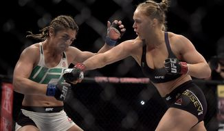 In this photo released by Inovafoto, Ronda Rousey, right, fights Brazil's Bethe Correia during their mixed martial arts bantamweight title fight at UFC 190, early Sunday, Aug. 2, 2015, in Rio de Janeiro, Brazil. Rousey knocked out Correia 34 seconds into the first round to win. (Alexandre Loureiro/Inovafoto via AP)