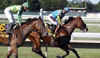 Jockey Victor Espinoza, right, on Triple Crown winner American Pharoah(4), smiles as he looks back at jockey Kent Desormeaux on Keen Ice (6) after American Pharoah won the Haskell Invitational horse race at Monmouth Park in Oceanport, N.J., Sunday, Aug. 2, 2015. Keen Ice was second. (AP Photo/Mel Evans)