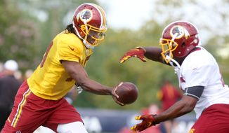 Washington Redskins quarterback Robert Griffin III hands the ball off to running back Alfred Morris during the team's NFL football training camp in Richmond, Va., Sunday, Aug. 2, 2015.   (AP Photo/Jason Hirschfeld)