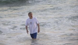 International Olympic Committee President Thomas Bach bathes in the waters of the Barra de Tijuca beach during a meeting with current and former Brazilian Olympic athletes in Rio de Janeiro, Brazil, Tuesday, Aug. 4, 2015. With the Olympic games being almost a year away, Bach played on the beach and bathed in the water, even after and AP investigation showed that all Olympic water venues had dangerously high viral levels, according to water safety experts who reviewed the data. (AP Photo/Silvia Izquierdo)