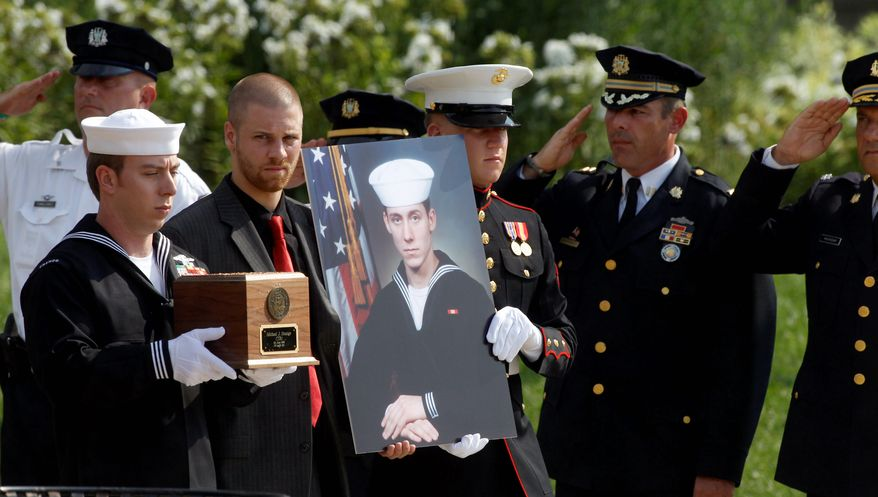 Petty Officer First Class Ian Regnier (above left) carries the remains of Petty Officer 1st Class Michael Joseph Strange, a cryptology technician, killed alongside members of SEAL Team 6 when their helicopter was shot down by a rocket-propelled grenade in Afghanistan in 2011 (bottom). The families of Strange and the other victims are demanding the White House release documents relevant to the incident. (Associated Press)