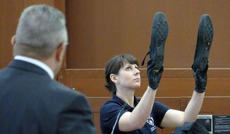 Charlotte-Mecklenburg Police Department Crime scene investigator C.L. Price holds a pair of shoes during day two of police officer Randall Kerrick's trial at the Mecklenburg County Courthouse in Charlotte, N.C., Tuesday, Aug. 4, 2015. Officer Kerrick faces voluntary manslaughter charges in the shooting death of Jonathan Ferrell. (Davie Hinshaw/The Charlotte Observer via AP, Pool)