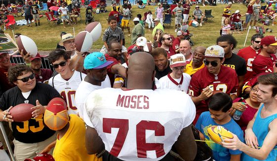 Washington Redskins' tackle Morgan Moses signs autograph for fans at an NFL training camp Thursday, Aug. 6, 2015, in Richmond, Va. The Washington Redskins and Houston Texans begin three days of joint workouts at the Redskins' training complex. (Rob Ostermaier/The Daily Press via AP) MANDATORY CREDIT