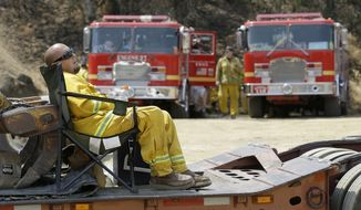 A firefighter rests at a staging area near Clearlake, Calif., Wednesday, Aug. 5, 2015. Thousands of firefighters battling an unruly Northern California wildfire were aided overnight by cooler temperatures and higher humidity, but the fire is still less than a quarter contained. (AP Photo/Jeff Chiu)