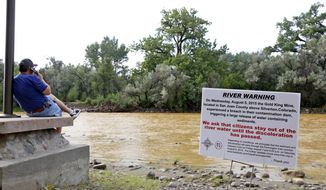 A warning sign from the city is displayed in front of the Animas River as orange sludge from a mine spill upstream flows past Berg Park in Farmington, N.M., on Aug. 8, 2015. About 1 million gallons of wastewater from Colorado's Gold King Mine began spilling into the Animas River on Wednesday when a cleanup crew supervised by the Environmental Protection Agency accidentally breached a debris dam that had formed inside the mine. The mine has been inactive since 1923. (Alexa Rogals/The Daily Times via AP) **FILE**