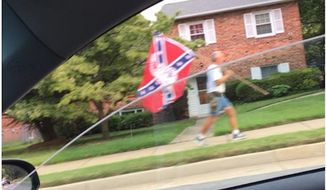 "A concerned citizen called police after spotting a man walking ""with purpose"" with a Confederate flag in Arlington, Va. (Image: screen grab from Twitter user @WayneWest)"