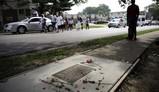 A memorial in memory of Michael Brown is seen in a sidewalk near where Brown was shot and killed as a parade in honor of Brown passes by Saturday, Aug. 8, 2015, in Ferguson, Mo. Sunday will mark one year since  Brown was shot and killed by Ferguson police officer Darren Wilson. (AP Photo/Jeff Roberson)