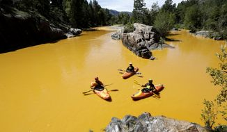 People kayak in the Animas River near Durango, Colo., on Thursday in water discolored by the Gold King Mine waste spill. (Associated Press)