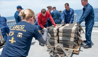 In this July 19, 2015 photo released by the U.S. Coast Guard, Coast Guard Cutter Stratton crew members secure cocaine bales from a self-propelled semi-submersible interdicted in international waters off the coast of Central America. The Coast Guard recovered more than 6 tons of cocaine from the 40-foot vessel. Cocaine seizures by the U.S. Coast Guard off Latin America have jumped to their highest levels in five years. Officials say Monday, Aug. 10, 2015, drug traffickers are increasingly turning to the sea to get their loads to U.S. markets. The $1.8 billion in seized cocaine comes after Washington restored the Coast Guard budget to its previous levels, following a 25 percent cut in operating costs in 2013. (Petty Officer 2nd Class LaNola Stone/U.S. Coast Guard via AP)