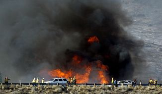 In this Friday, July 17, 2015, file photo, firefighters battle a wildfire along the Cajon Pass, near San Bernadino, Calif., as the fast-moving flames swept across a Southern California freeway. A spate of drone sightings near firefighting aircraft is fueling calls for more oversight and self-policing in the skies. (Terry Pierson/The Orange County Register via AP, File)