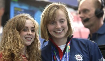 United States' swimmer Katie Ledecky, right, poses for a photo with fans ahead of the final night of racing at the Swimming World Championships in Kazan, Russia, Sunday, Aug. 9, 2015. Ledecky won five gold medals at the 2015 championships. (AP Photo/Michael Sohn)