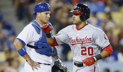 Washington Nationals' Ian Desmond, right, crosses the plate in front of Los Angeles Dodgers catcher A.J. Ellis after hitting a solo home run during the eighth inning of a baseball game, Monday, August 10, 2015, in Los Angeles. (AP Photo/Danny Moloshok)