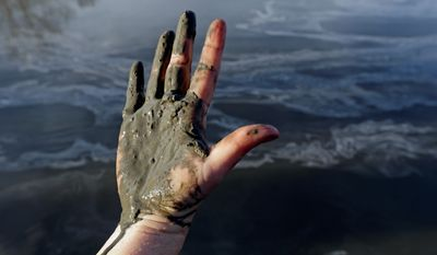 Amy Adams' hand is covered with coal ash after she pulls it from the Dan River in North Carolina. She is campaign coordinator of Appalachian Voices, a grass-roots environmental organization concerned about toxic sludge. (Associated Press)