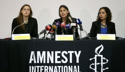 Amnesty International's Charlotte Phillips, center, speaks during a press conference about Syrian refugees' medical treatment, in Beirut, Lebanon, Wednesday May 21, 2014. Amnesty said tens of thousands of Syrians lack access to hospital treatment in Lebanon, leaving their chronic conditions and serious illnesses untreated. The crisis is due to a lack of funding for medical care for Syrians who fled to neighboring Lebanon, where health care is privatized and expensive, Amnesty said. Some ill Syrians simply have been turned away.(AP Photo/Hussein Malla)
