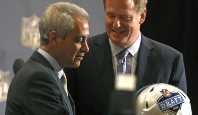 NFL Commissioner Roger Goodell, right, presents Chicago Mayor Rahm Emanuel with an NFL Draft helmet as he announces that the draft is returning to Chicago next year, at a news conference Tuesday, Aug. 11, 2015, in Schaumburg, Ill. Goodell and Mayor Emanuel made the announcement at the NFL owners' meetings. It's the second straight year for Chicago after a long run at Radio City Music Hall in New York. (AP Photo/Christian K. Lee)