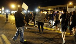 Crowds chant in the street along West Florissant Avenue, Monday, Aug. 10, 2015, in Ferguson, Mo. Ferguson was a community on edge again Monday, a day after a protest marking the anniversary of Michael Brown's death was punctuated with gunshots. (AP Photo/Jeff Roberson)