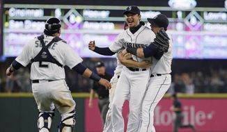 Seattle Mariners starting pitcher Hisashi Iwakuma, second from right, is greeted by teammates, including catcher Jesus Sucre, left, after Iwakuma threw a no-hitter in a baseball game against the Baltimore Orioles, Wednesday, Aug. 12, 2015, in Seattle. The Mariners won 3-0. (AP Photo/Ted S. Warren)