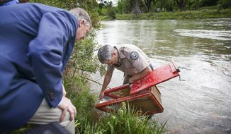 Colorado Governor John Hickenlooper, left, looks at a fish trap on the banks of the Animas River  that is being held by Colorado Parks and Wildlife's Aquatic Biologist Jim White in the waters of the river contaminated last week by a massive mine blowout above Silverton, Colo. The Governor toured the area before giving an address to area residents regarding the status ofAnimas River Tuesday, Aug. 11, 2015.  (Shaun Stanley/The Durango Herald via AP)