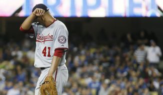 Washington Nationals starting pitcher Joe Ross leaves the field as he is pulled from the game after Los Angeles Dodgers' Yasiel Puig hit a triple to score Jimmy Rollins, Alberto Callaspo and Yasmani Grandal during the fifth inning of a baseball game, Tuesday, Aug. 11, 2015, in Los Angeles. (AP Photo/Danny Moloshok)