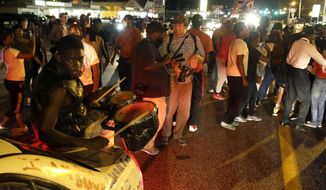 """Protesters gather along West Florissant Avenue during a demonstration in Ferguson, Mo., Tuesday, Aug. 11, 2015. The St. Louis suburb has seen demonstrations for days marking the anniversary of the death of 18-year-old Michael Brown, whose shooting death by a Ferguson police officer sparked a national """"Black Lives Matter"""" movement. Tuesday was the fifth consecutive night a crowd gathered on West Florissant, the thoroughfare that was the site of massive protests and rioting after Brown was killed.  (AP Photo/Jeff Roberson)"""