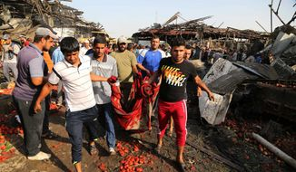 People evacuate the body of a victim killed from a bombing in Jameela market in the Iraqi capital's crowded Sadr City neighborhood Baghdad, Iraq, Thursday, Aug. 13, 2015. A massive truck bomb ripped through a popular Baghdad food market in a predominantly Shiite neighborhood in the early morning hours on Thursday, killing at least 62 people, police officials said. (AP Photo/Karim Kadim)
