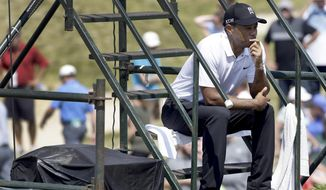 Tiger Woods sits on some stairs on the second hole during the second round of the PGA Championship golf tournament Friday, Aug. 14, 2015, at Whistling Straits in Haven, Wis. (AP Photo/Brynn Anderson)