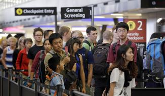 In this Tuesday, Aug. 11, 2015, file photo, travelers wait in a security line at Seattle-Tacoma International Airport, in Seattle. (AP Photo/Elaine Thompson)