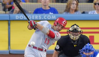 Cincinnati Reds' Joey Votto hits an RBI double as Los Angeles Dodgers catcher Yasmani Grandal, right, watches along with home plate umpire Paul Nauert during the first inning of a baseball game, Friday, Aug. 14, 2015, in Los Angeles. (AP Photo/Mark J. Terrill)