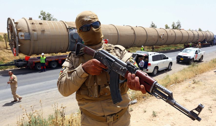 A Kurdish Peshmerga fighter stands guard as new equipment arrives at Kalak refinery on the outskirts of Irbil, Iraq, as Kurdish authorities try to help ease the fuel shortage. (Associated Press)