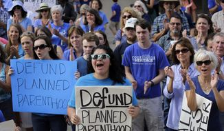 Erica Canaut, center, cheers as she and other anti-abortion activists rally on the steps of the Texas Capitol to condemn the use in medical research of tissue samples obtained from aborted fetuses, Tuesday, July 28, 2015, in Austin, Texas. (AP Photo/Eric Gay) ** FILE **