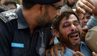 A Pakistani police officer comforts a man recovered from the rubble at the site of a suicide bombing in Shadi Khan, some 80 kilometers (50 miles) northwest from Pakistani capital, Sunday, Aug. 16, 2015.  A pair of suicide bombers detonated their explosives at the home of an anti-Taliban provincial minister, killing him and more than a dozen others in eastern Pakistan, officials said. (AP Photo/Ghulam Shabbir)